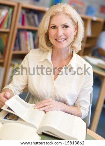 Mature female student studying in library - stock photo