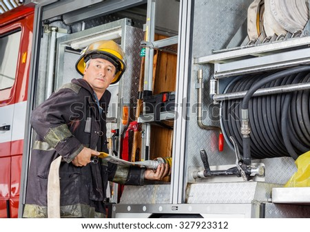 Mature fireman looking away while fixing hose in truck at fire station