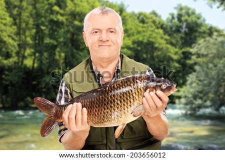 Mature fisherman showing his catch standing by a river outdoors - stock photo