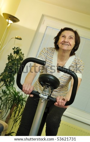 Mature fitness woman exercise on spinning bicycle at home - stock photo