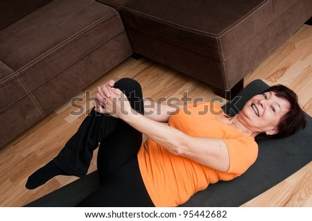 Mature fitness woman exercising at home - stock photo