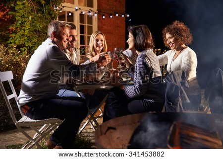 Mature Friends Enjoying Outdoor Evening Meal Around Firepit - stock photo