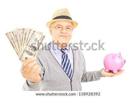 Mature gentleman holding a piggy bank and US dollars isolated on white background - stock photo