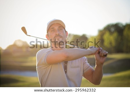 Mature golf player posing with brassie. Man with sports hat on going to play professional golf on green course. - stock photo