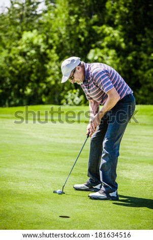 Mature Golfer on a Golf Course - stock photo
