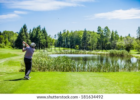 Mature Golfer on a Golf Course Taking a Swing on the Start. - stock photo