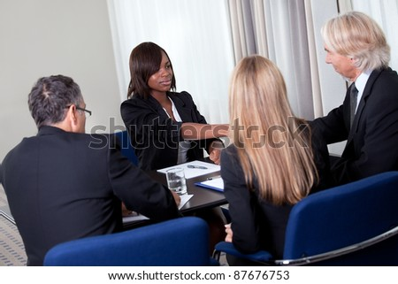Mature group of business managers conducting job interview shaking hands with applicant at a table in meeting room - stock photo