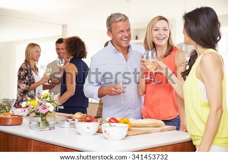 Mature Guests Being Welcomed At Dinner Party By Friends - stock photo