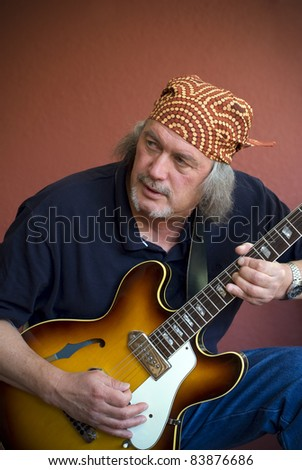 Mature guitarist with sunburst hollow body guitar and bandana - stock photo