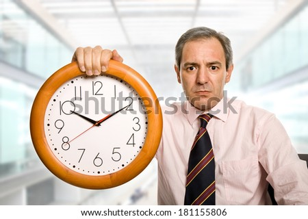 mature handsome businessman holding a clock at the office - stock photo