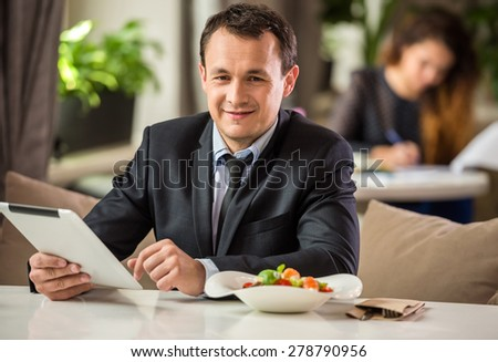Mature handsome businessman sitting in cafe and using digital tablet. - stock photo