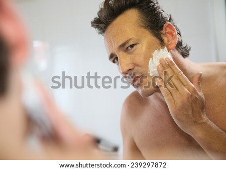 Mature handsome man shaving in front of mirror - stock photo