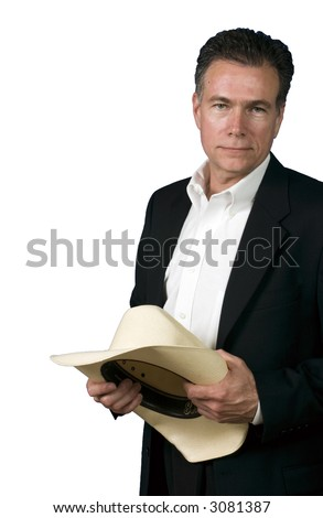Mature, handsome, white male wearing a black suite and a white shirt with a cowboy hat held in his hands. - stock photo