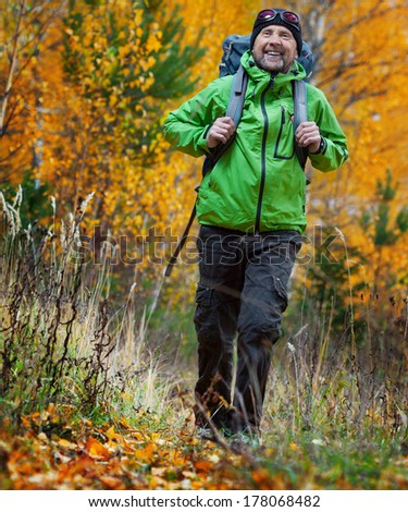 Mature happy backpacker walking in an autumn forest