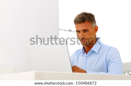 Mature happy businessman working with laptop - stock photo