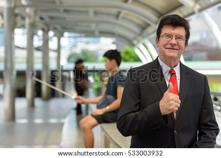 Mature happy Caucasian businessman giving thumb up and sitting on train station at Bangkok city