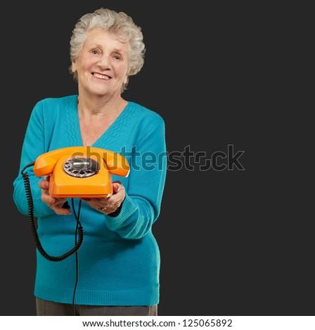 Mature Happy Woman Holding Telephone On Black Background - stock photo