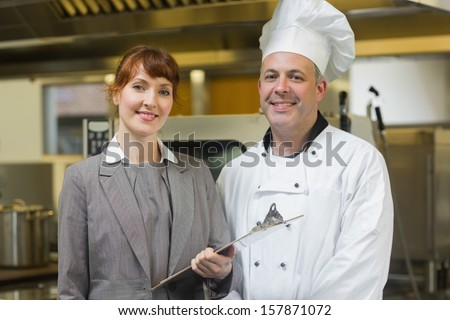 Mature head cook posing with the female manager in a professional kitchen - stock photo