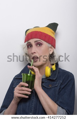 Mature hipster woman in fashionable hat drinking alcohol cocktail over white background. Beautiful senior woman in jeans shirt.