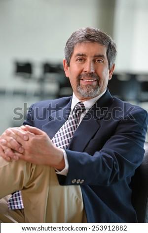 Mature Hispanic businessman smiling inside office building - stock photo