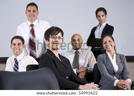 Mature Hispanic businesswoman leading group of younger office workers - stock photo