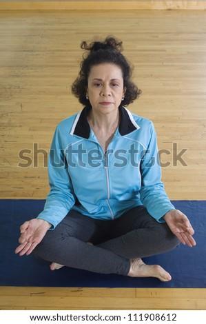Mature hispanic woman meditating in lotus position - stock photo