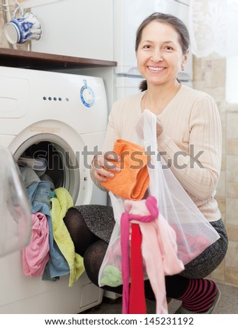 mature housewife loading the washing machine with laundry bag