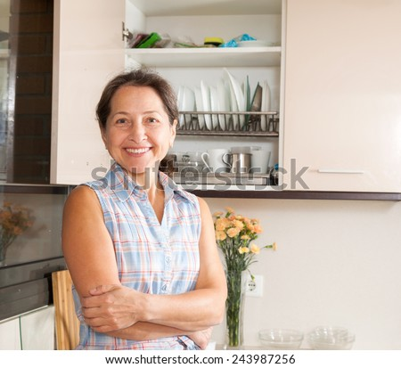 Mature housewife standing at domestic kitchen - stock photo