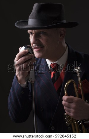 Mature Jazz man singing into a microphone and holding a trumpet