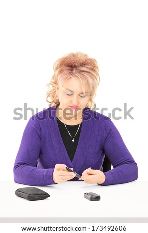 Mature lady checking her blood sugar level, isolated on white background - stock photo