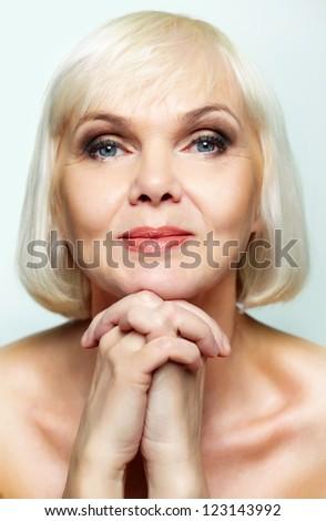 Mature lady looking calmly at camera - stock photo