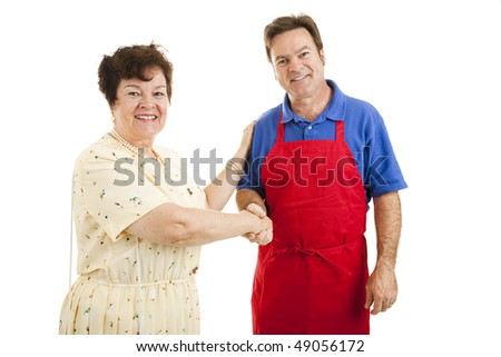 Mature lady shopping, shaking hands with a sales clerk or other type of worker.  Isolated on white. - stock photo