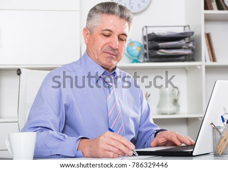 Mature lawyer examines important documents in the office of the law firm