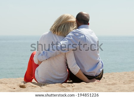 Mature lovers sitting on sand at beach and enjoying the view - stock photo