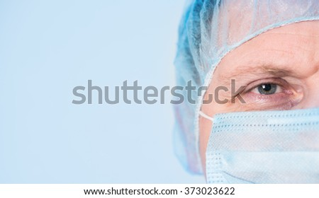 Mature mail surgeon in hospital closeup portrait on blue background with copyspace. - stock photo