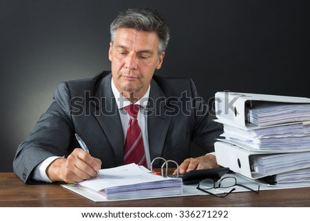 Mature male accountant checking invoice with calculator at desk against gray background - stock photo