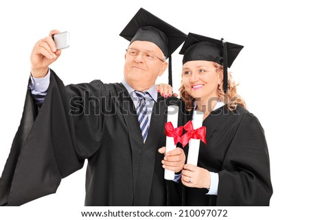 Mature male and female in graduation gowns taking a selfie isolated on white background - stock photo