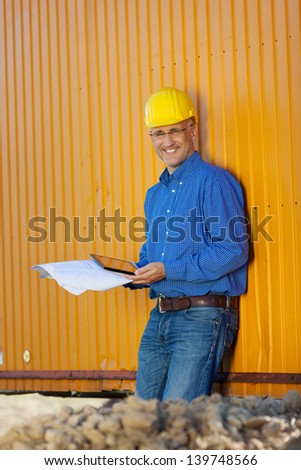 Mature male architect holding blueprints and digital tablet against trailer - stock photo