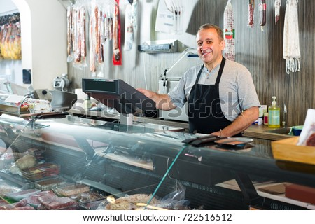 Mature male butcher with assortment of wurst and smoked meat at counter