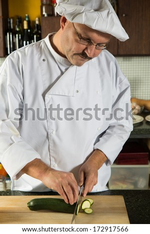 Mature male chef cutting the vegetables