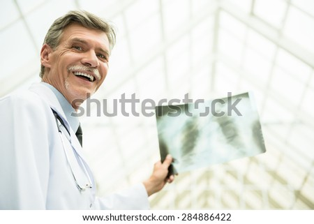 Mature male doctor looking at X-ray. Healthcare and medicine concept. - stock photo