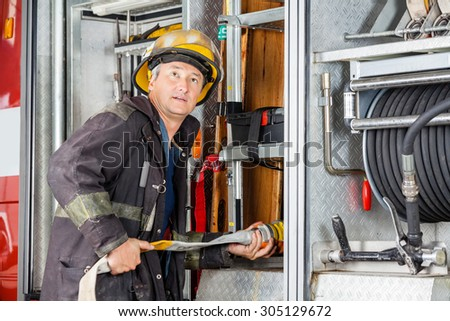 Mature male firefighter looking away while adjusting hose in truck at fire station