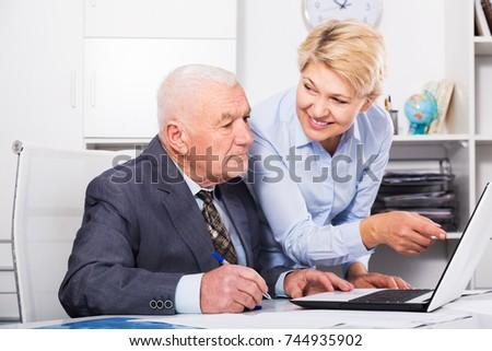 Mature male manager and female secretary working effectively together in office
