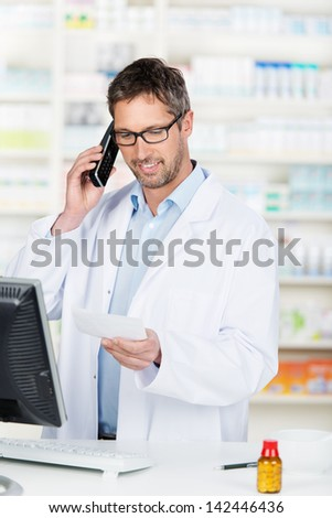 Mature male pharmacist using phone at pharmacy counter - stock photo