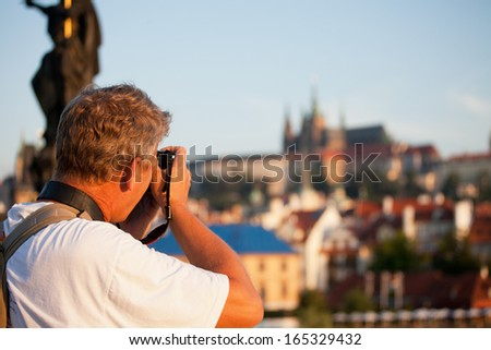 mature male photographer photographs morning Prague - stock photo