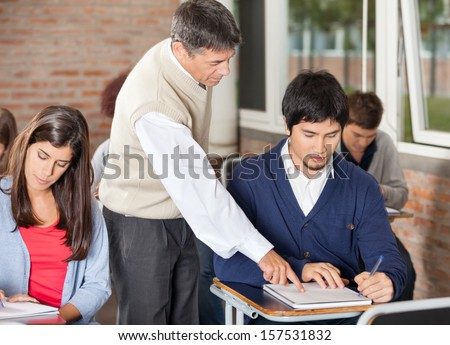 Mature male professor explaining test to student in classroom - stock photo