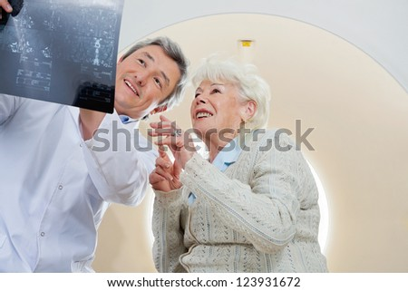 Mature male radiologist with an elderly female patient looking at x-ray - stock photo