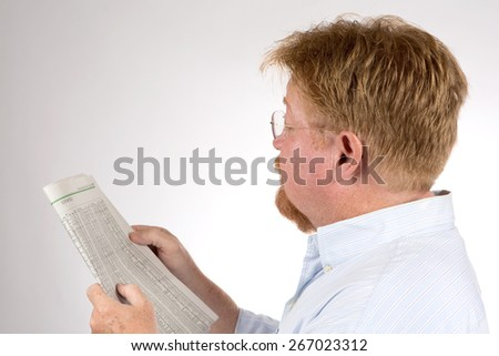 Mature male reads the stock market report in the newspaper to glean financial information and improve his investments. - stock photo