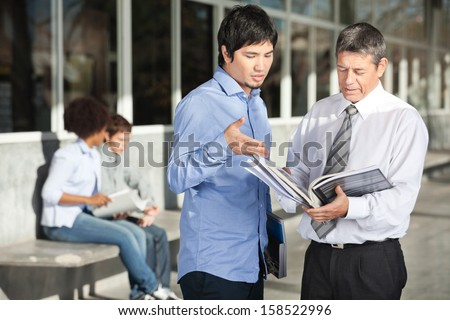Mature male teacher holding books while discussing with student on college campus - stock photo