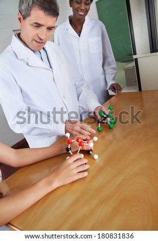 Mature male teacher looking at molecular structure at desk with female colleague in background - stock photo